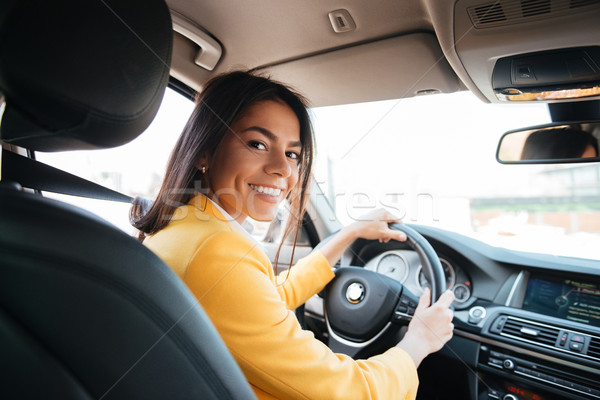 Back view of a confident smiling woman driving car Stock photo © deandrobot