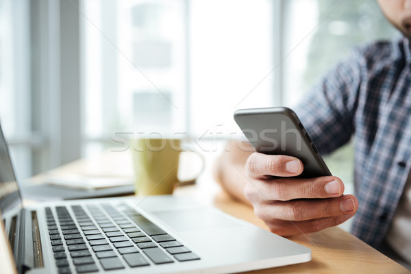 Cropped image of young man using laptop computer and phone. Stock photo © deandrobot