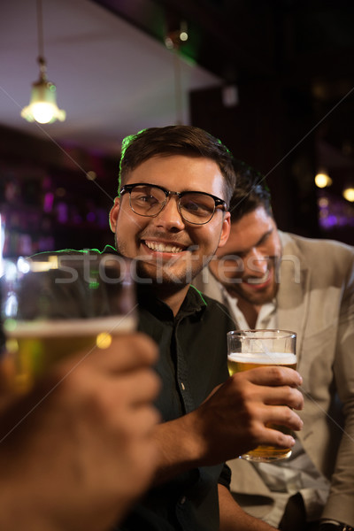 Smiling man having beer with his friends in a pub Stock photo © deandrobot
