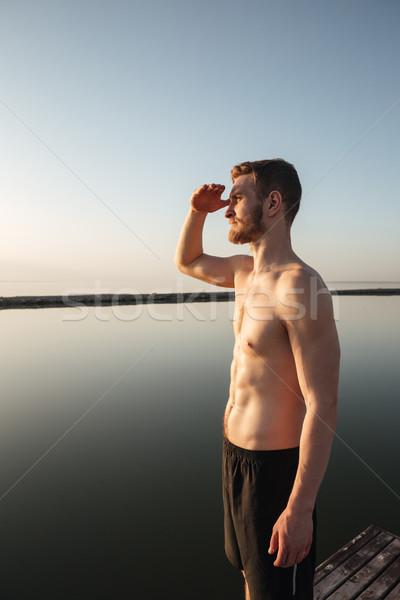 Sports man standing at the beach and looking far away Stock photo © deandrobot