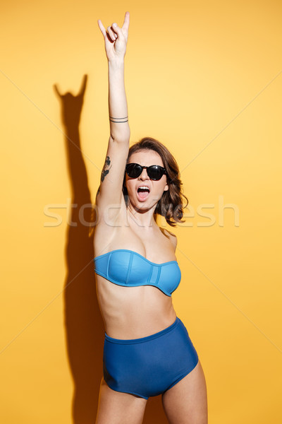 Screaming young woman in swimwear make rock gesture. Stock photo © deandrobot