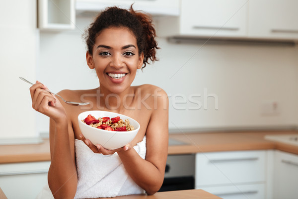 Cheerful young african woman eating strawberry with muesli. Stock photo © deandrobot