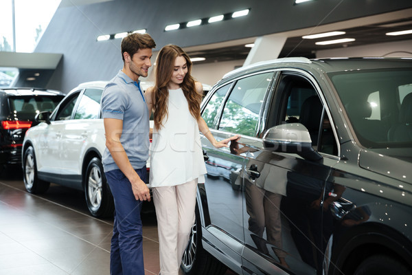 Beautiful young couple standing at the car dealership Stock photo © deandrobot