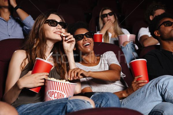 Cheerful friends sitting in cinema watch film Stock photo © deandrobot