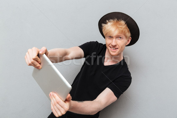 Stock photo: Caucasian man play games by tablet computer.
