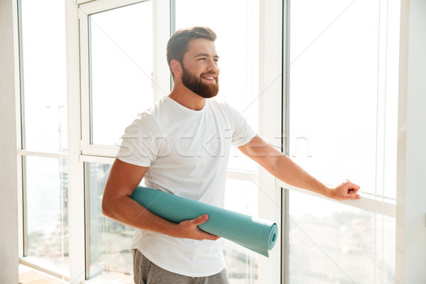 Smiling bearded man standing with fitness mat near the window Stock photo © deandrobot