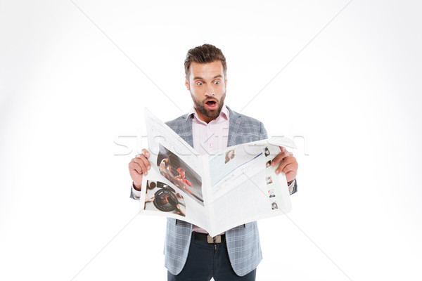Shocked young man reading gazette. Stock photo © deandrobot