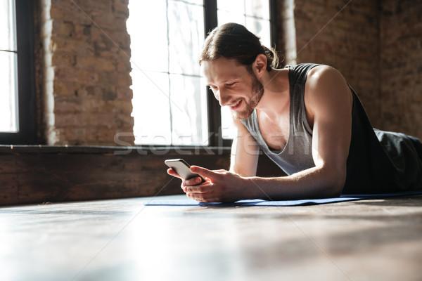 Mosolyog fókuszált sportoló mobiltelefon fektet fitnessz Stock fotó © deandrobot