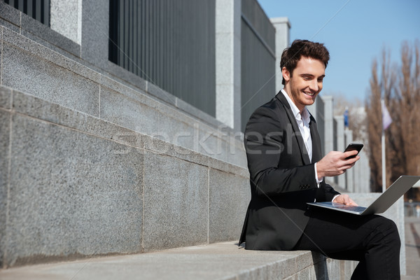 Stock photo: Smiling young businessman sitting outdoors chatting by phone.