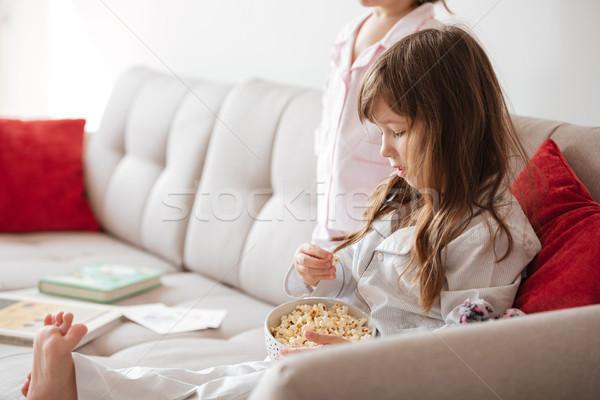 Aranyos lány eszik pattogatott kukorica otthon kislány Stock fotó © deandrobot