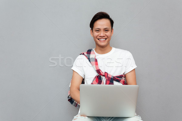 Happy young asian man over grey background using laptop Stock photo © deandrobot