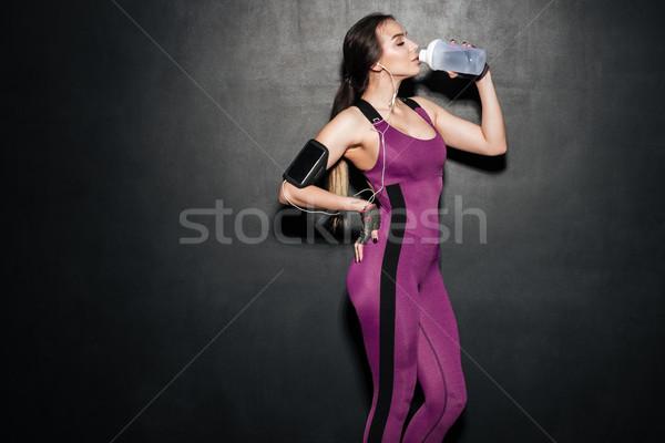 Nő ivóvíz hallgat zene izolált fiatal Stock fotó © deandrobot