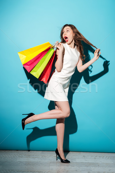 Stock photo: Smiling woman in dress walking with colorful shopping bags