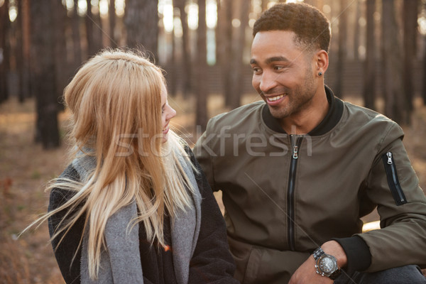 Smiling loving couple sitting outdoors in the forest. Stock photo © deandrobot