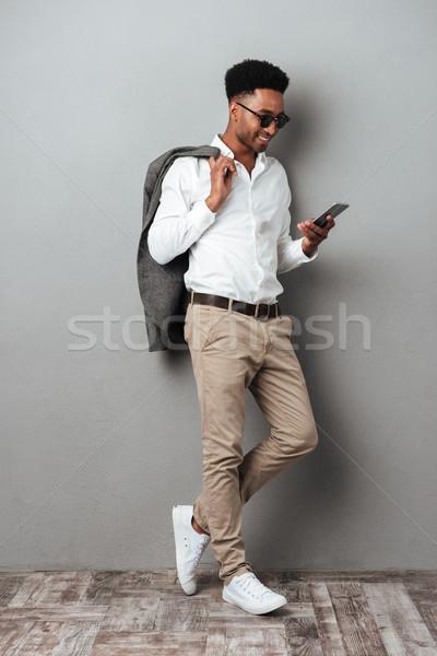 Uśmiechnięty Afryki człowiek okulary kurtka Zdjęcia stock © deandrobot