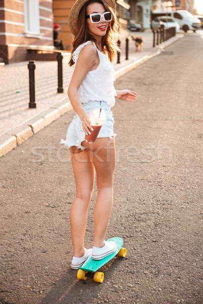 Happy young woman on skateboard outdoors holding cocktail. Stock photo © deandrobot
