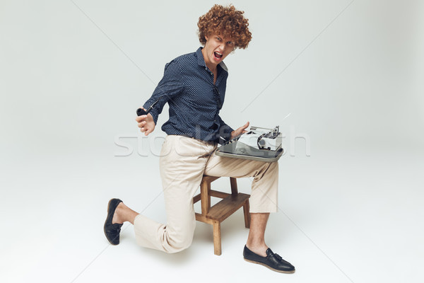 Screaming angry retro man holding typewriter. Stock photo © deandrobot