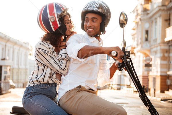 Side view of happy african couple rides on modern motorbike Stock photo © deandrobot