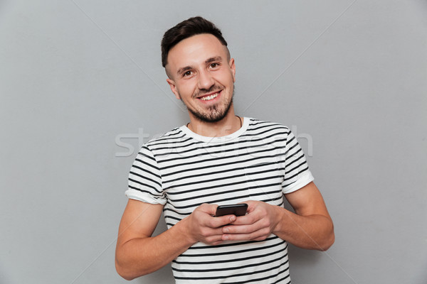 Smiling young man chatting by mobile phone Stock photo © deandrobot