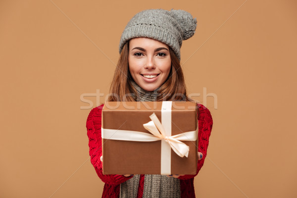 Attractive young woman in winter clothes giving you gift box Stock photo © deandrobot