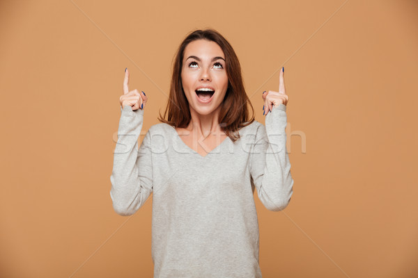Young happy attractive brunette girl pointing with two fingers a Stock photo © deandrobot