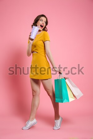 Full-length shot of young caucasian lady shopping and talking on phone isolated Stock photo © deandrobot