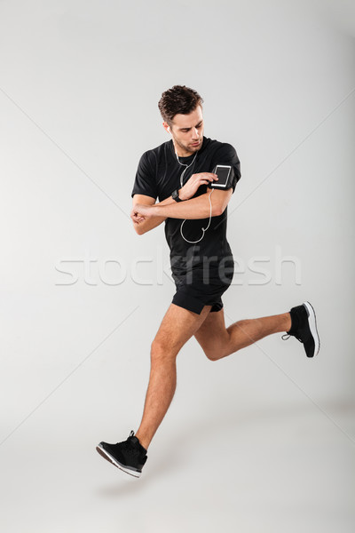 Full length portrait of a handsome young man athlete Stock photo © deandrobot