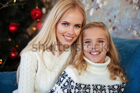 Stock photo: Close-up photo of little girl in knitted sweater kiss her mother