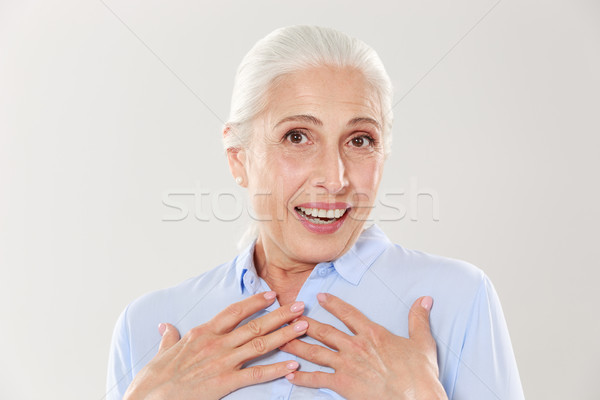 Fotó meglepődött öreg hölgy kezek mellkas néz Stock fotó © deandrobot