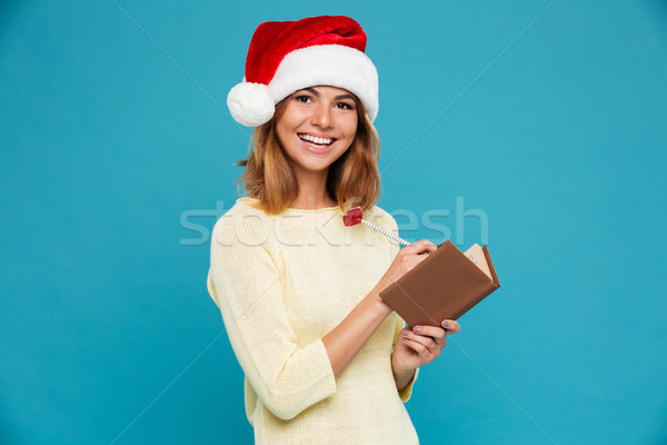 Close-up portrait of cheerful brunette woman in Santa's hat writing notes while looking at camera Stock photo © deandrobot