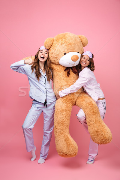 Friends women in pajamas with teddy bear showing thumbs up. Stock photo © deandrobot