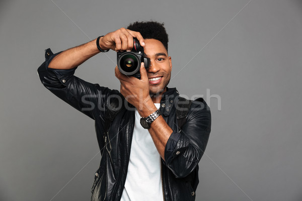Portrait of a smiling afro american guy in leather jacket Stock photo © deandrobot
