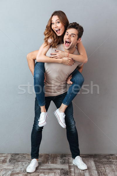 Full length portrait of a happy man carrying girlfriend Stock photo © deandrobot