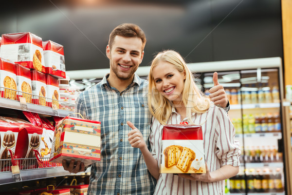 Stock photo: Cheerful couple buying food for christmas