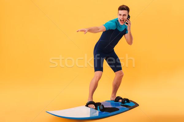 Afbeelding glimlachend surfer surfboard praten smartphone Stockfoto © deandrobot