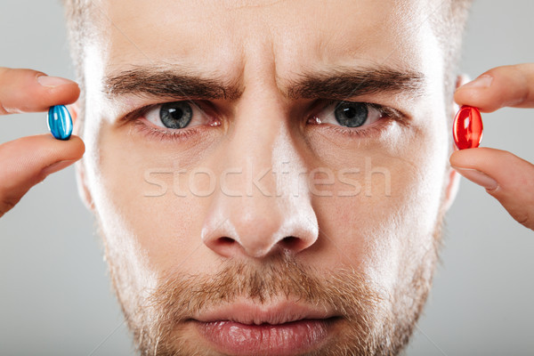 Portré komoly férfi tart kettő kapszulák Stock fotó © deandrobot