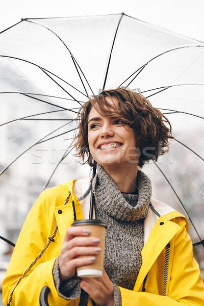 Alegre mulher jovem capa de chuva imagem caminhada ao ar livre Foto stock © deandrobot
