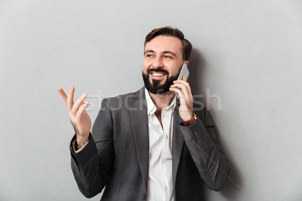 Positive businesslike guy in formal wear mobile chatting gesturi Stock photo © deandrobot