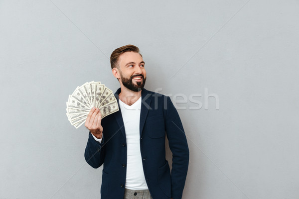 Happy bearded man in business clothes holding money Stock photo © deandrobot