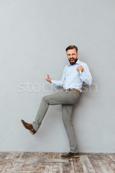 Full-length image of happy screaming bearded man in business clothes Stock photo © deandrobot