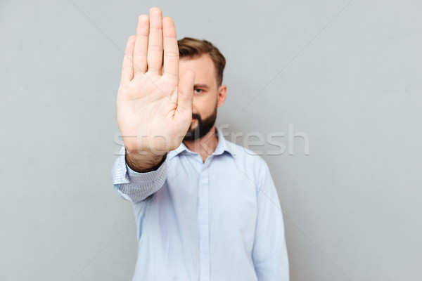 Image of Bearded man in business clothes showing stop gesture Stock photo © deandrobot