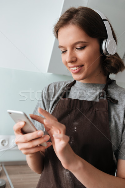 Portrait of a smiling young woman in headphones wearing apron Stock photo © deandrobot