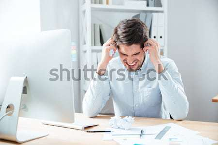 Confused concentrated man working with papers and laptop Stock photo © deandrobot
