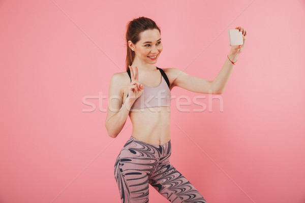 Stock photo: Smiling sportswoman making selfie on smartphone and showing peace gesture