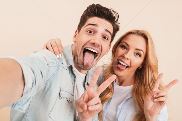 Photo of amusing happy couple man and woman hugging and taking s Stock photo © deandrobot