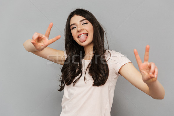 Pretty cute young lady showing peace gesture. Stock photo © deandrobot