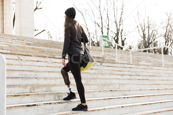 Photo from back of disabled running girl with prosthetic leg in  Stock photo © deandrobot
