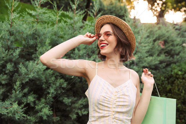 Happy woman in dress, straw hat and sunglasses posing Stock photo © deandrobot