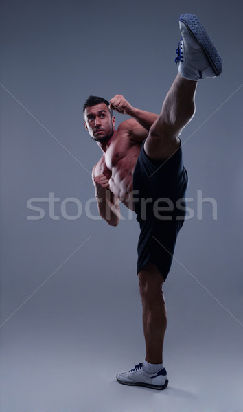 Portrait of a muscular man practicing body combat over gray background Stock photo © deandrobot