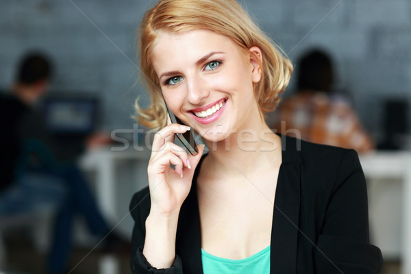 Happy businesswoman talking on the phone in office Stock photo © deandrobot